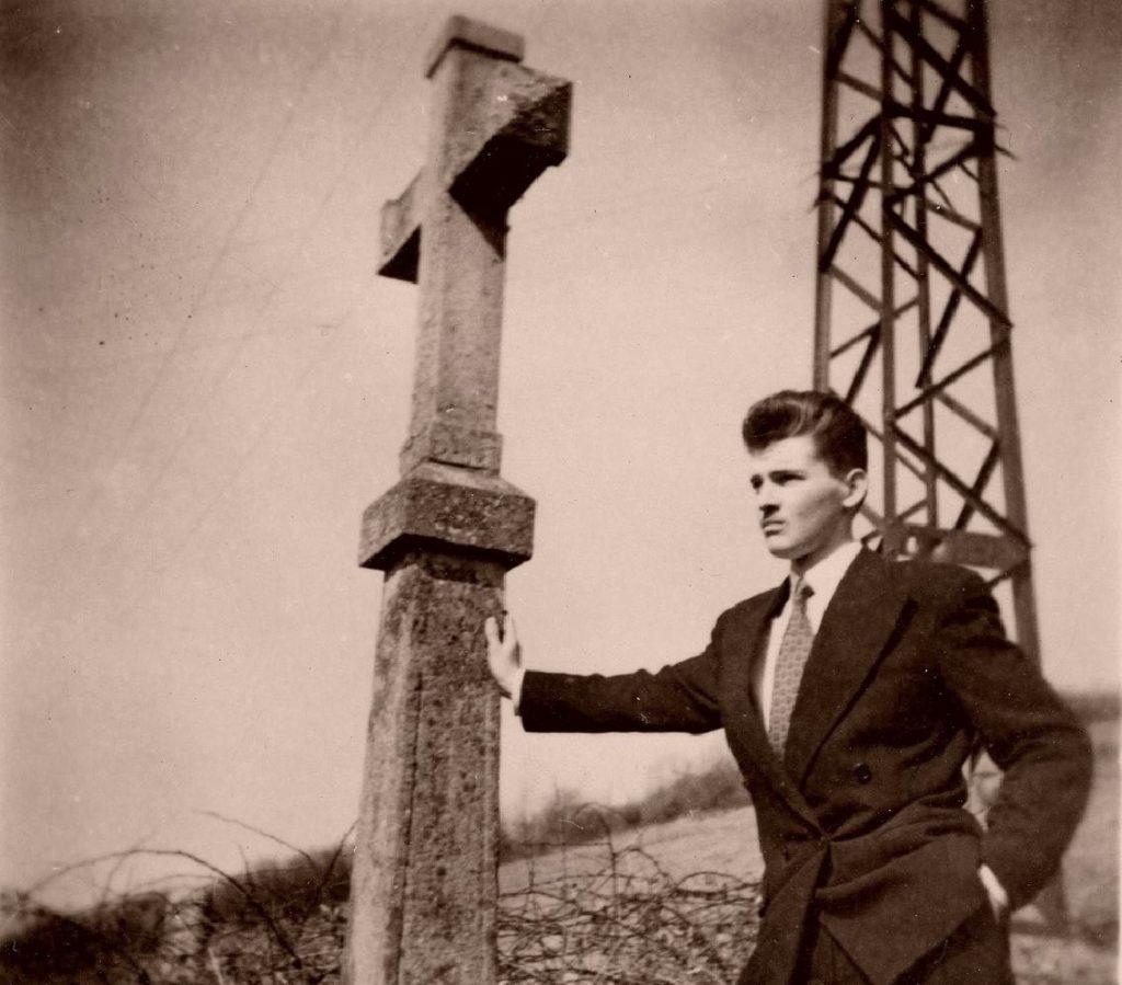 Photo d'André Grandjean au pied de l'ancien calvaire