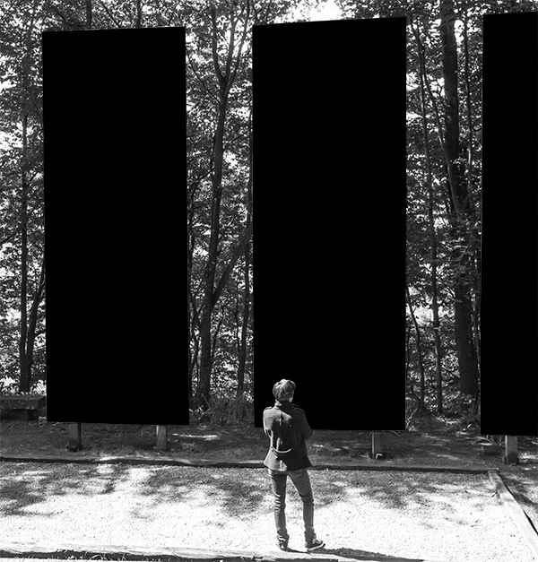 Julien Cuny devant les trois panneaux