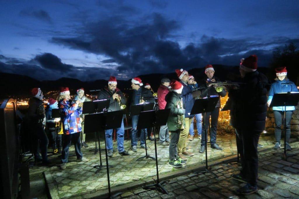 Photo des musiciens de l'Ensemble de Cuivres avec leurs bonnets lumineux de Père Noël et en fond les lumières de la ville et celles du ciel peu après le coucher du soleil